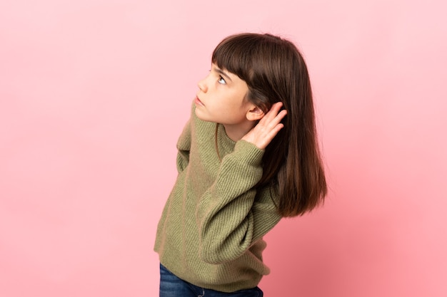 Little girl isolated on pink wall listening to something by putting hand on the ear