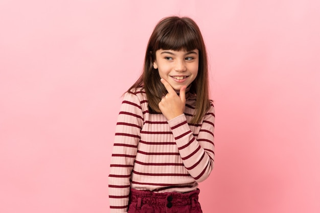 Little girl isolated on pink wall looking to the side and smiling