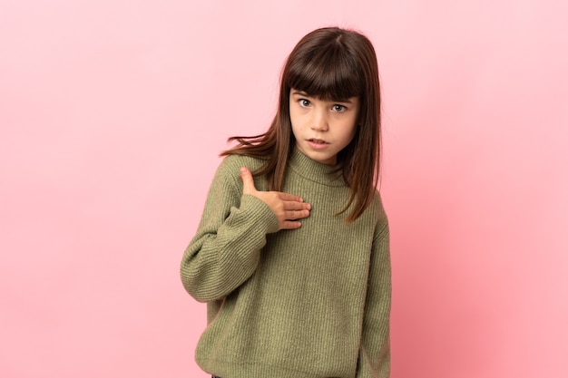 Little girl isolated on pink wall pointing to oneself