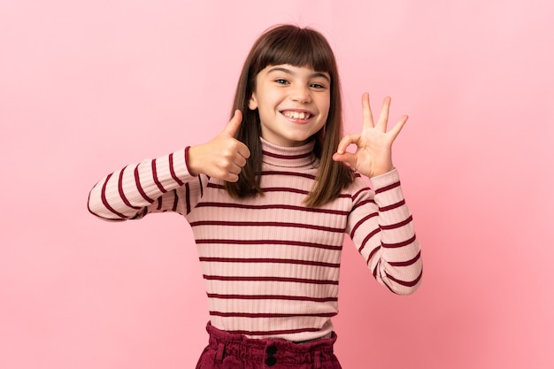 Little girl isolated on pink wall showing ok sign and thumb up gesture