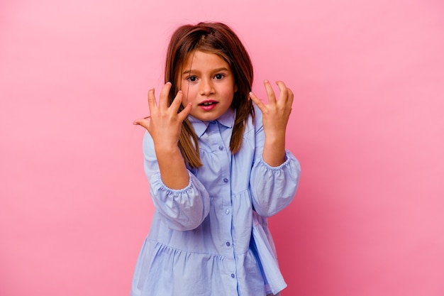 Little girl isolated on pink wall  upset screaming with tense hands