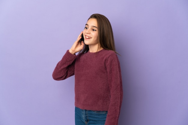 Little girl isolated on purple background keeping a conversation with the mobile phone