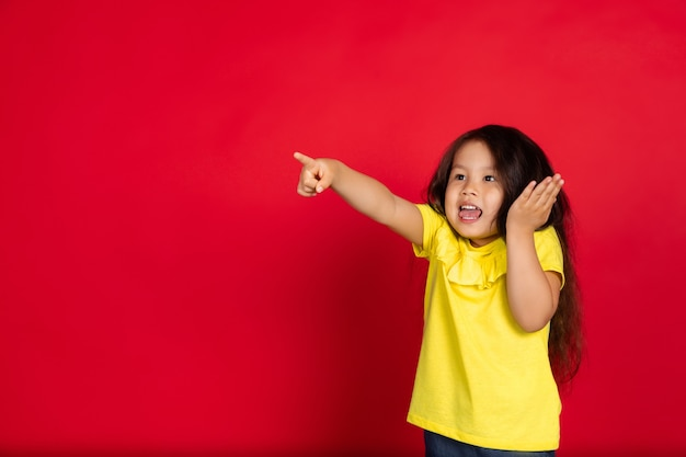 Little girl isolated on red, happy