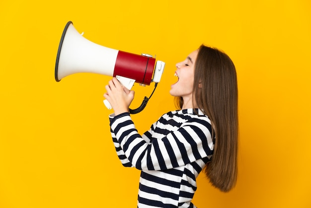 Little girl isolated shouting through a megaphone to announce something in lateral position