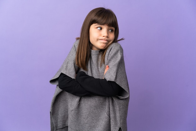 Little girl over isolated wall making doubts gesture while lifting the shoulders
