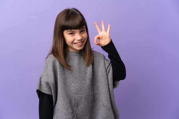 Little girl over isolated wall showing ok sign with fingers