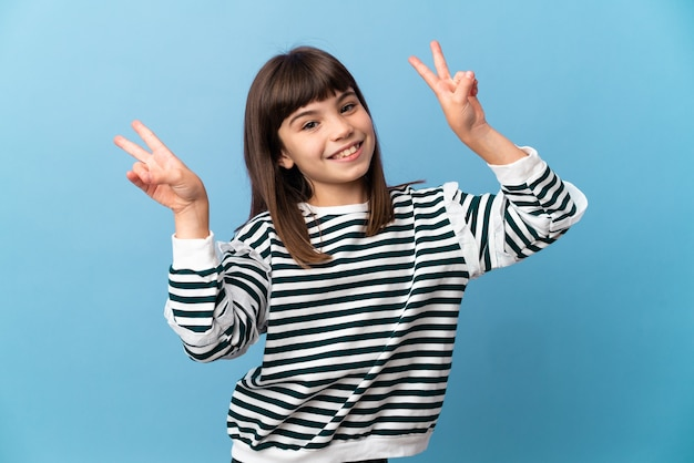 Little girl over isolated wall showing victory sign with both hands