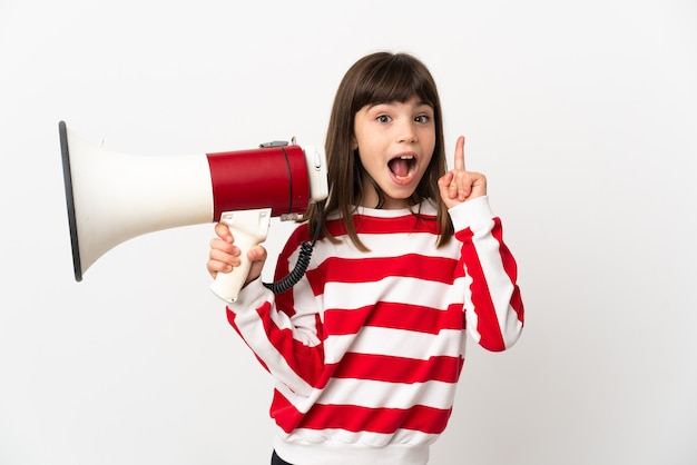 Little girl isolated on white background holding a megaphone and intending to realizes the solution