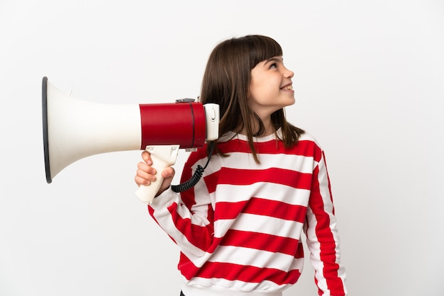 Little girl isolated on white background holding a megaphone and looking up while smiling