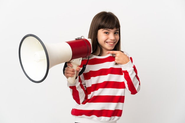 Little girl isolated on white background holding a megaphone and pointing side