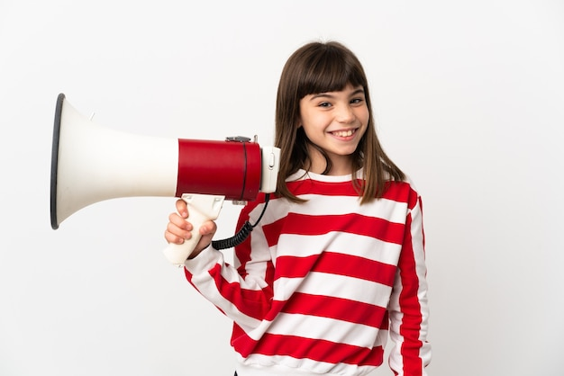 Little girl isolated on white background holding a megaphone and smiling a lot