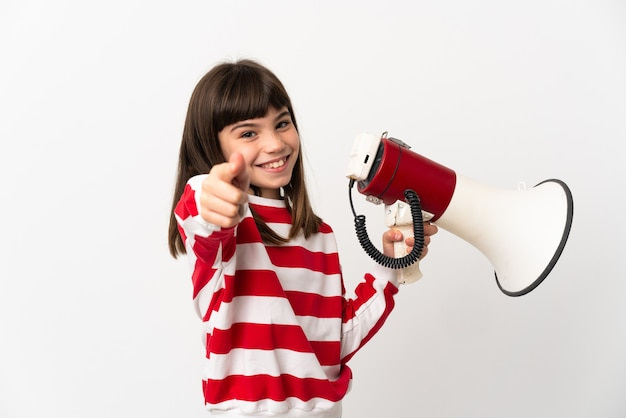 Little girl isolated on white background holding a megaphone and smiling while pointing to the front