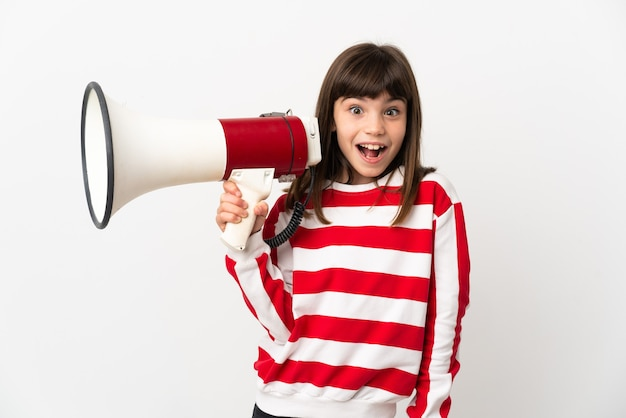 Little girl isolated on white background holding a megaphone and with surprise expression