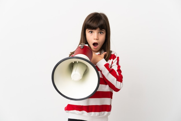 Little girl isolated on white background shouting through a megaphone with surprised expression