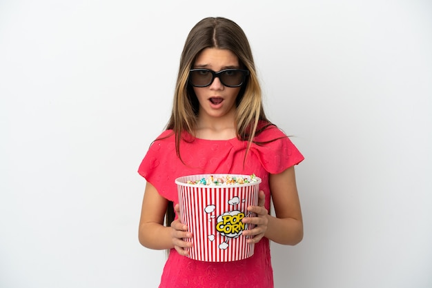 Little girl over isolated white background surprised with 3d glasses and holding a big bucket of popcorns