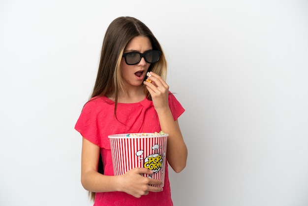 Little girl over isolated white background with 3d glasses and holding a big bucket of popcorns while looking side