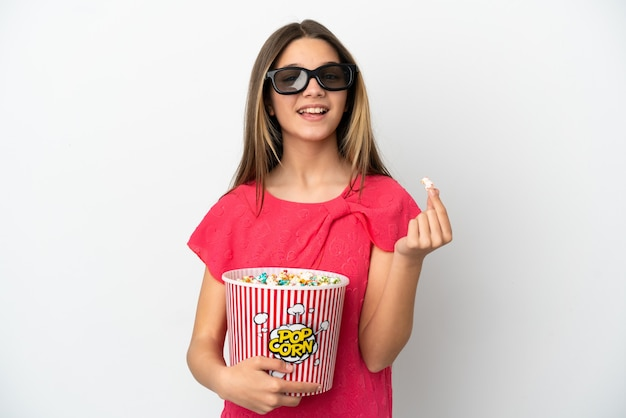 Little girl over isolated white background with 3d glasses and holding a big bucket of popcorns