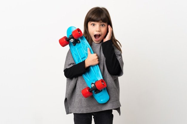 Little girl isolated on white background with a skate and doing surprise gesture