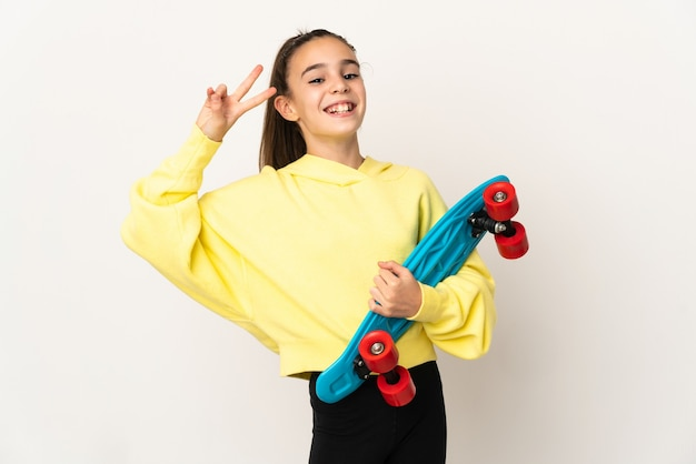 Little girl isolated on white background with a skate with happy expression