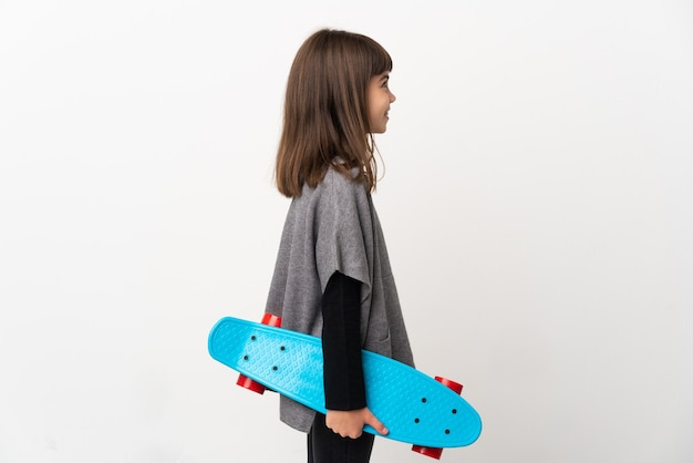 Little girl isolated on white background with a skate
