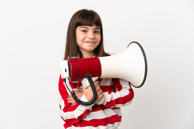 Little girl isolated on white wall holding a megaphone and smiling