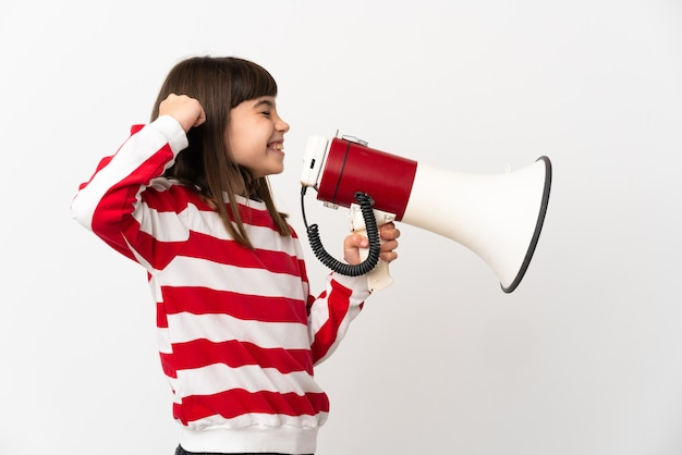 Little girl isolated on white wall shouting through a megaphone to announce something in lateral position