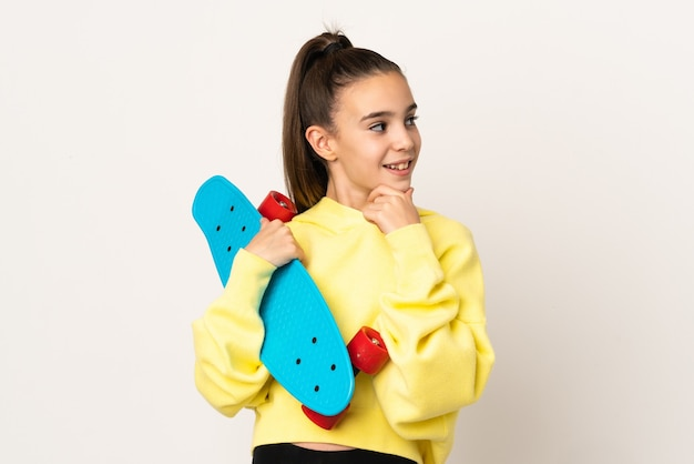 Little girl isolated on white wall with a skate and looking lateral