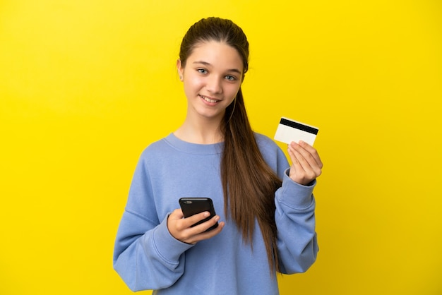 Little girl over isolated yellow background buying with the mobile with a credit card