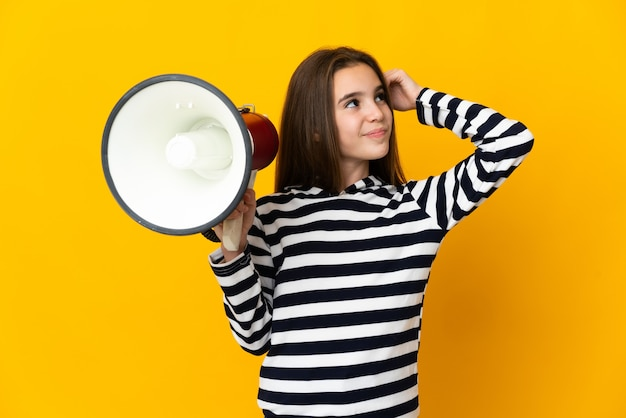 Little girl isolated on yellow background holding a megaphone and having doubts