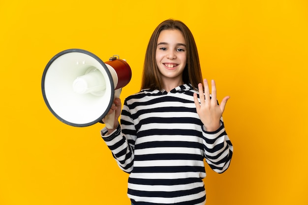 Little girl isolated on yellow background holding a megaphone and inviting to come with hand