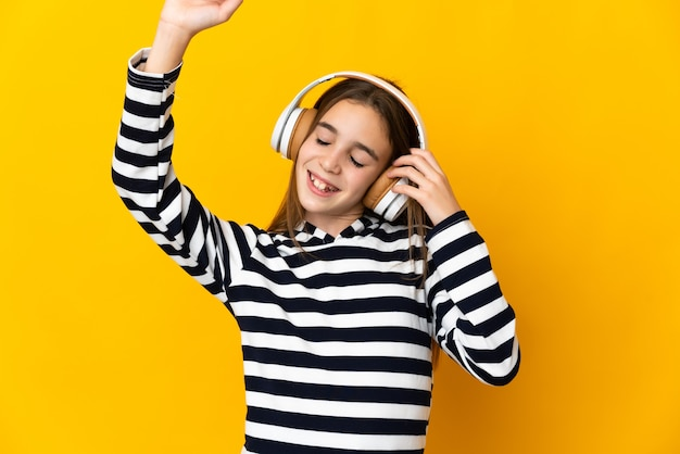 Little girl isolated on yellow background listening music and dancing