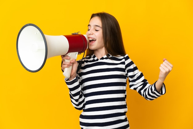 Little girl isolated on yellow background shouting through a megaphone to announce something in lateral position