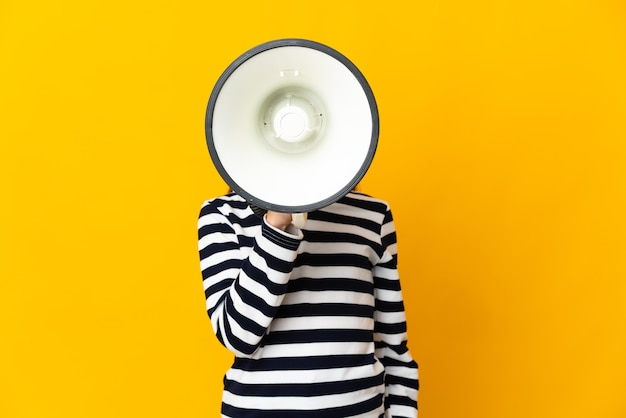 Little girl isolated on yellow background shouting through a megaphone to announce something