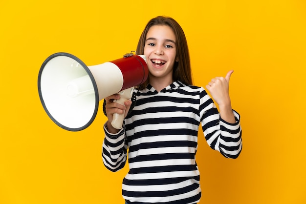 Little girl isolated on yellow background shouting through a megaphone and pointing side