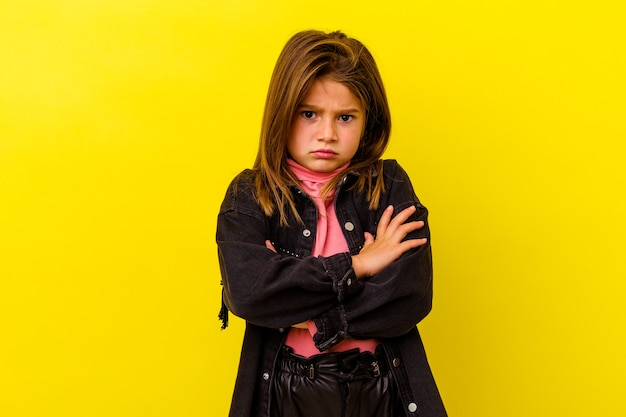 Little girl isolated on yellow wall blows cheeks, has tired expression facial expression concept