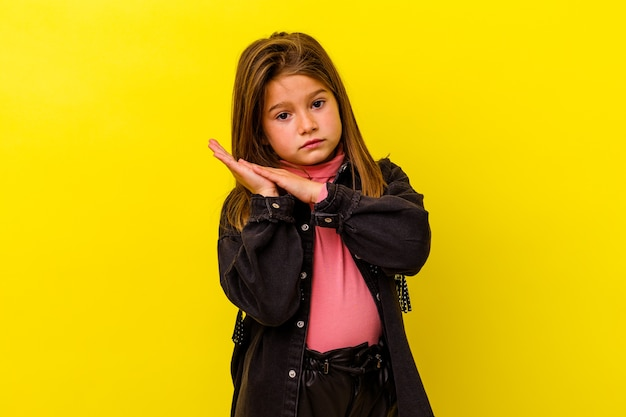 Little girl isolated on yellow wall feeling energetic and comfortable, rubbing hands confident