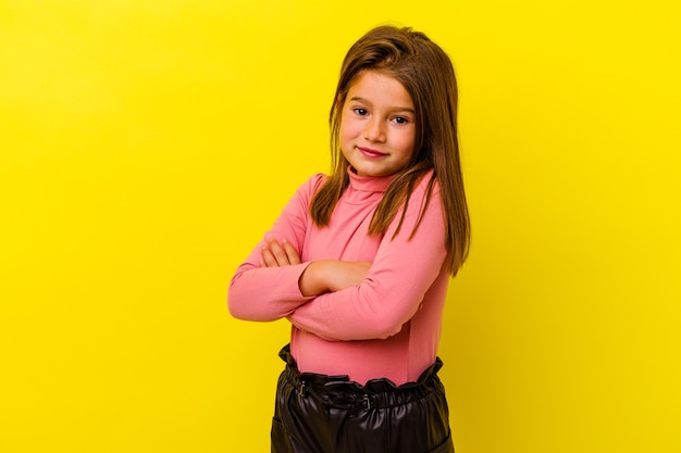 Little girl isolated on yellow wall happy, smiling and cheerful