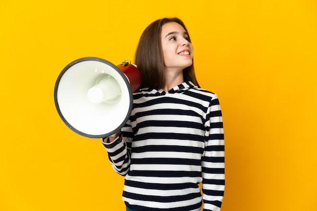 Little girl isolated on yellow wall holding a megaphone and looking up while smiling