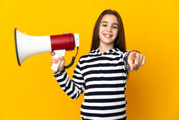 Little girl isolated on yellow wall holding a megaphone and smiling while pointing to the front