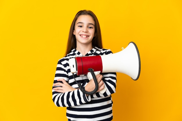Little girl isolated on yellow wall holding a megaphone and smiling