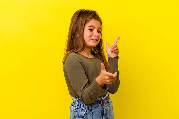 Little girl isolated on yellow wall joyful laughing a lot