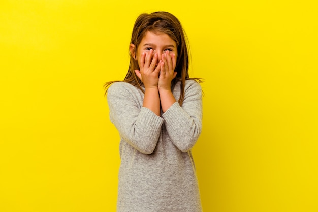 Little girl isolated on yellow wall laughing about something, covering mouth with hands