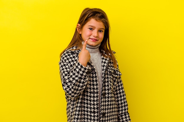 Little girl isolated on yellow wall pointing with finger at you as if inviting come closer