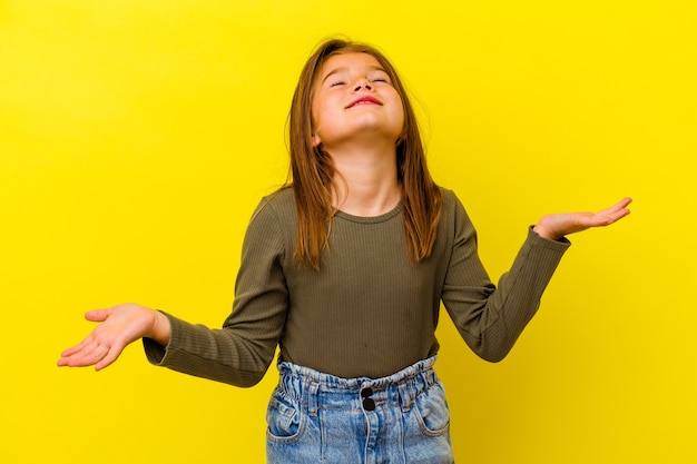 Little girl isolated on yellow wall relaxed and happy laughing, neck stretched showing teeth