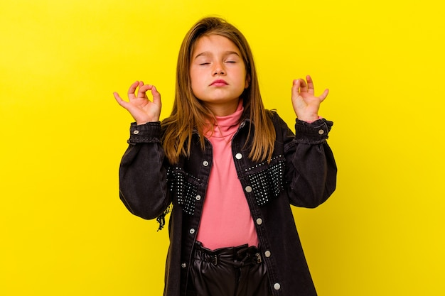 Little girl isolated on yellow wall relaxes after hard working day, she is performing yoga
