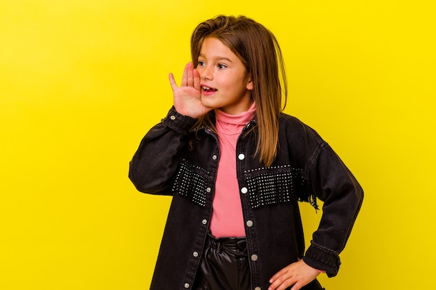 Little girl isolated on yellow wall shouting excited to front