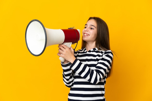 Little girl isolated on yellow wall shouting through a megaphone to announce something