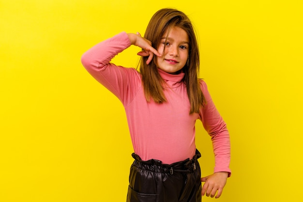 Little girl isolated on yellow wall showing a mobile phone call gesture with fingers
