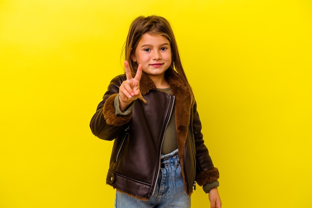 Little girl isolated on yellow wall showing number two with fingers