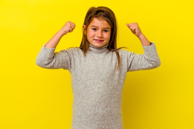 Little girl isolated on yellow wall showing strength gesture with arms